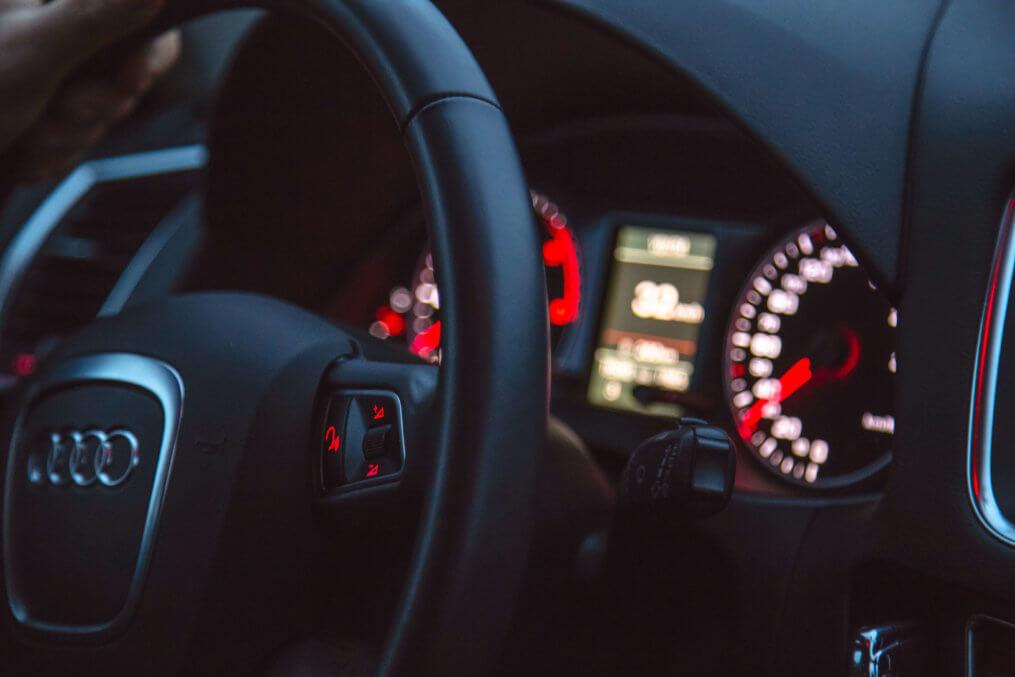 Imagem com foco no volante e painel aceso de um carro, funcionando à base de baterias automotivas.