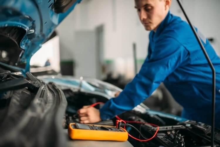 mecânico arrumando uma bateria arriada
