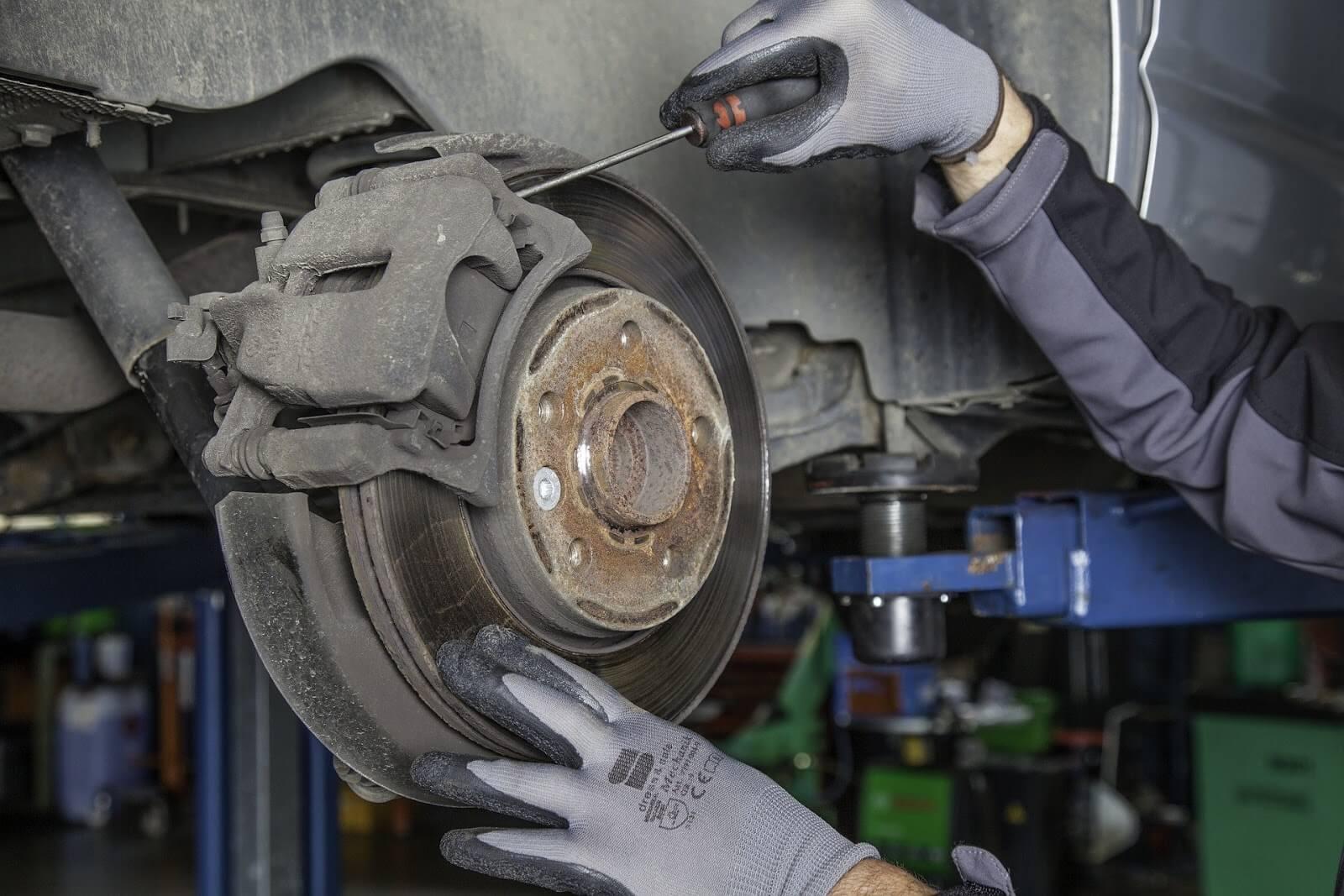 Mãos com luvas fazendo alterações na pastilha de freio de um carro