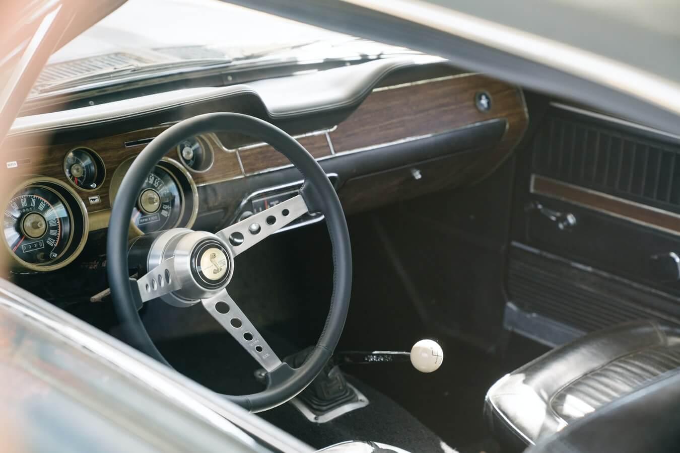 Imagem mostra parte interna de um veículo antigo, volantes, bancos e marcha de carro