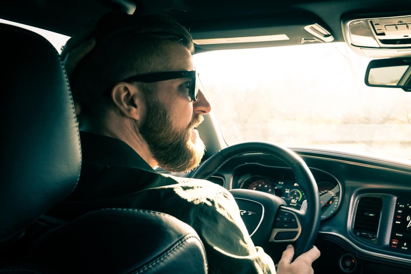 Imagem mostra um homem dentro de um carro, dirigindo