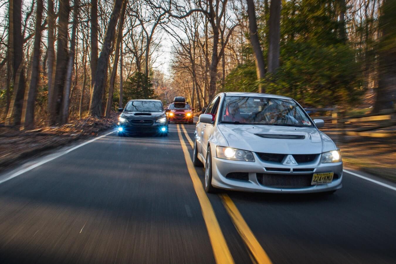 Carros esportivos andando em estrada