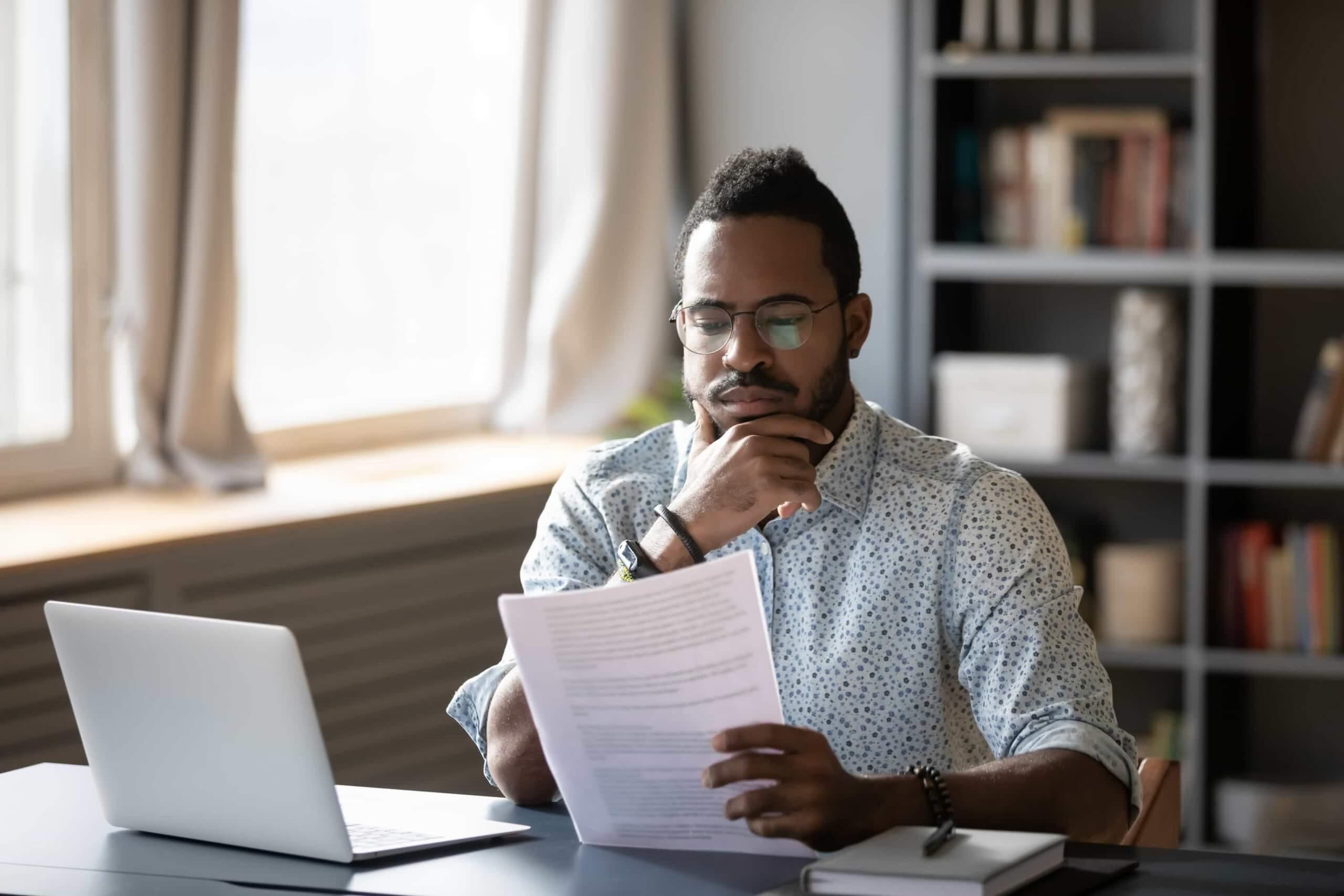 A imagem mostra um homem sentando, segurando e lendo um documento impresso.